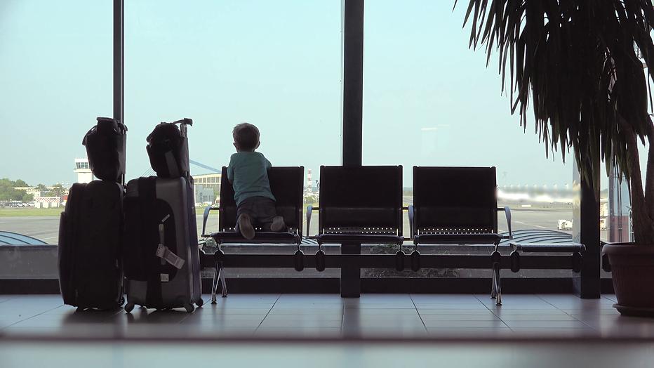 little-child-looking-on-big-window-waiti