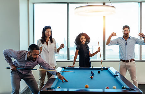 Young men and woman playing billiards at