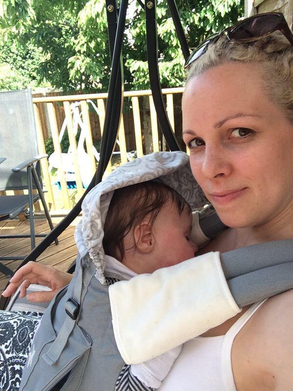 Blonde haired Woman looking at the camera slightly smiling with a baby in an ergo carrier on her front dark haired baby is asleep