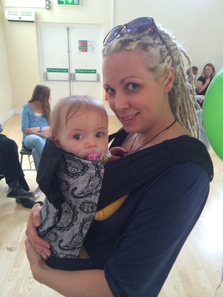 Blonde haired woman holding a baby in a carrier on her front, both looking at the camera, other people are in the background