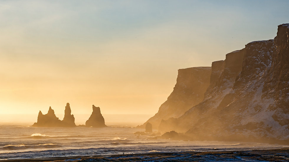 Rock formations in the water at Reynisfjara black sand beach in Iceland at sunset