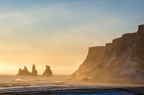 Reynisdrangar basalt sea stacks at Reynisfjara black sand beach, near the village of Vík, at sunset in Iceland