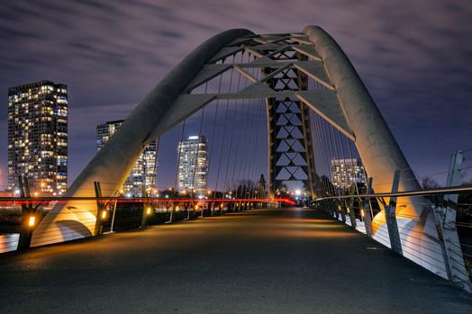 Biker under Toronto arch bridge at night