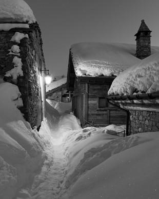 Alpine village after dusk, path through the snow