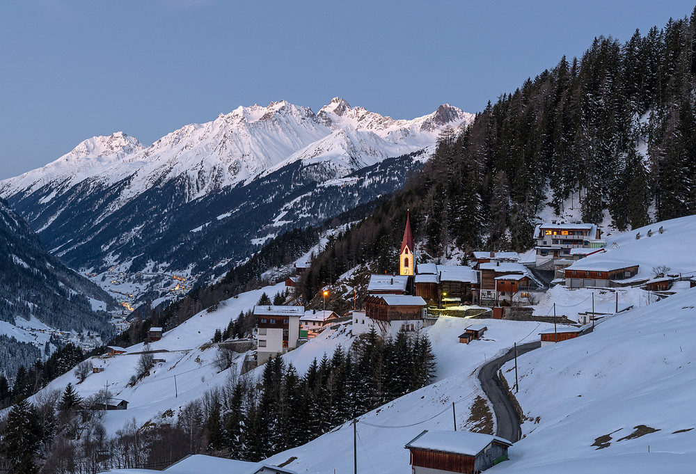 Alpine village in the Austrian province of Tyrol at dawn. Snowy mountains of the Alps in the background, church and houses among evergreen forest in the foreground.
