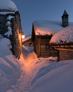 Winter evening path between wooden chalets in an Alpine village