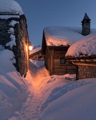Winter evening path between wooden chalets in an Alpine village