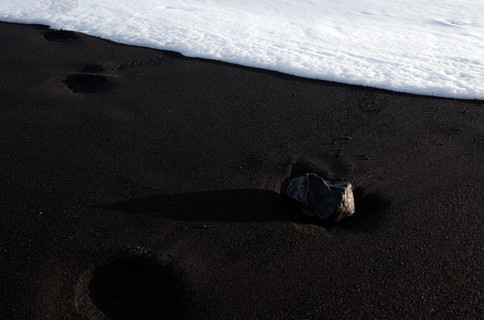Wave rolling up to a lonely rock at the sea shore of Reynisfjara beach