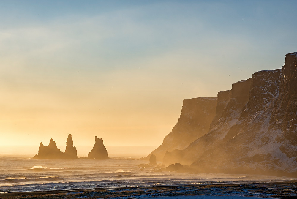 "Waves rolling onto the black sand of Reynisfjara beach at ""golden hour"". Snow covered mountains and Reynisdrangar rock formations in the background, couple walking along shore. Near the village of Vik, Southern Region, Iceland."