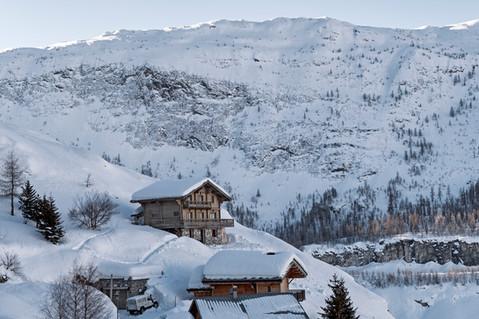 Winter morning in an Alpine village, mountain backdrop