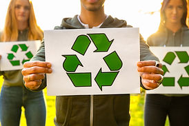 young-volunteers-holding-recycling-symbo