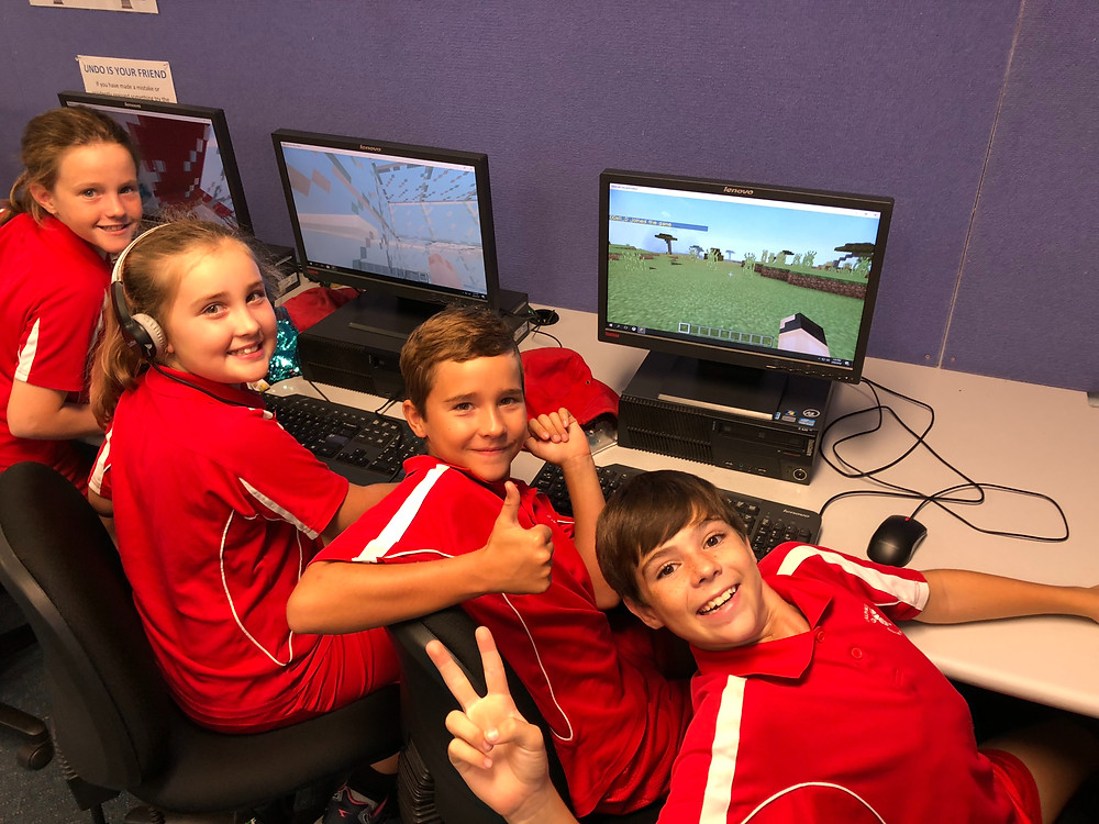 4/5 students playing minecraft in the computer room