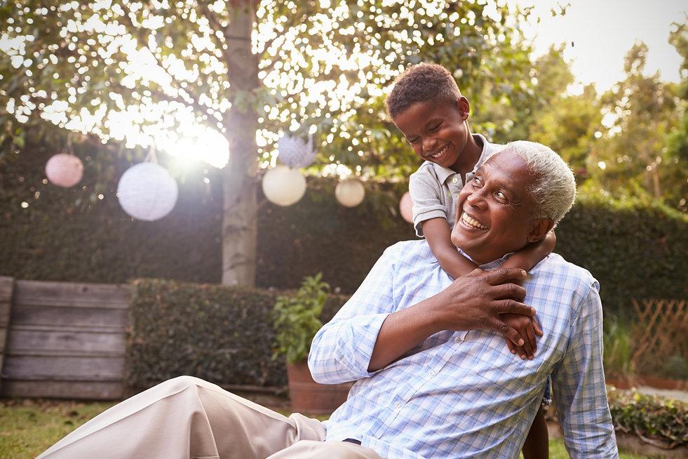 Young black boy embracing grandfather si