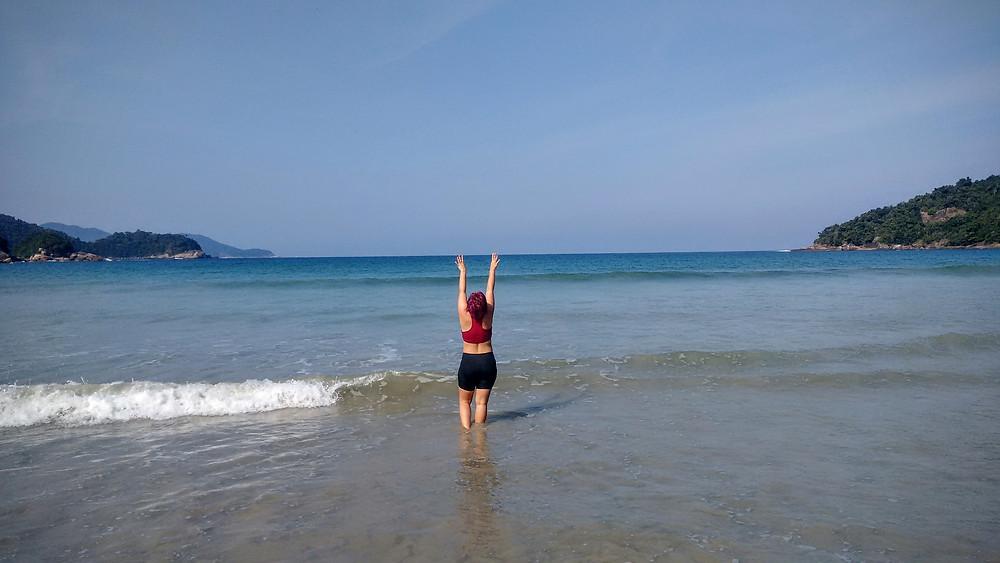 Uma mulher de costas levantando os braços para Dois Rios