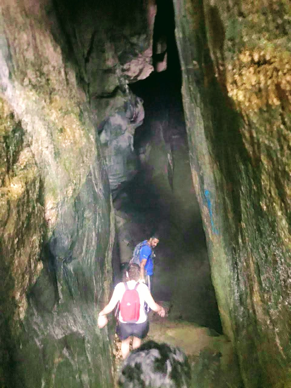 duas pessoas entrando em uma gruta