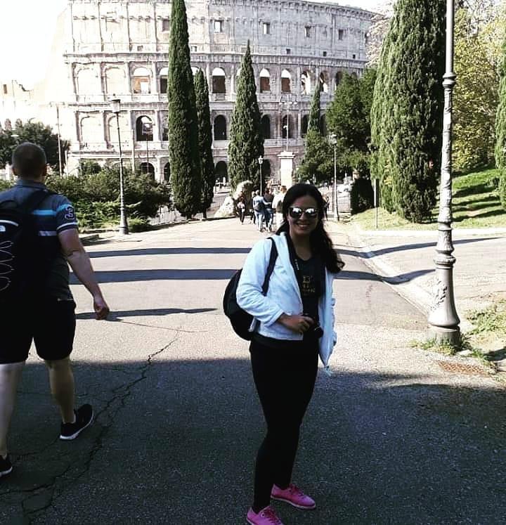 Mulher tirando foto em uma praça em frente ao Coliseu