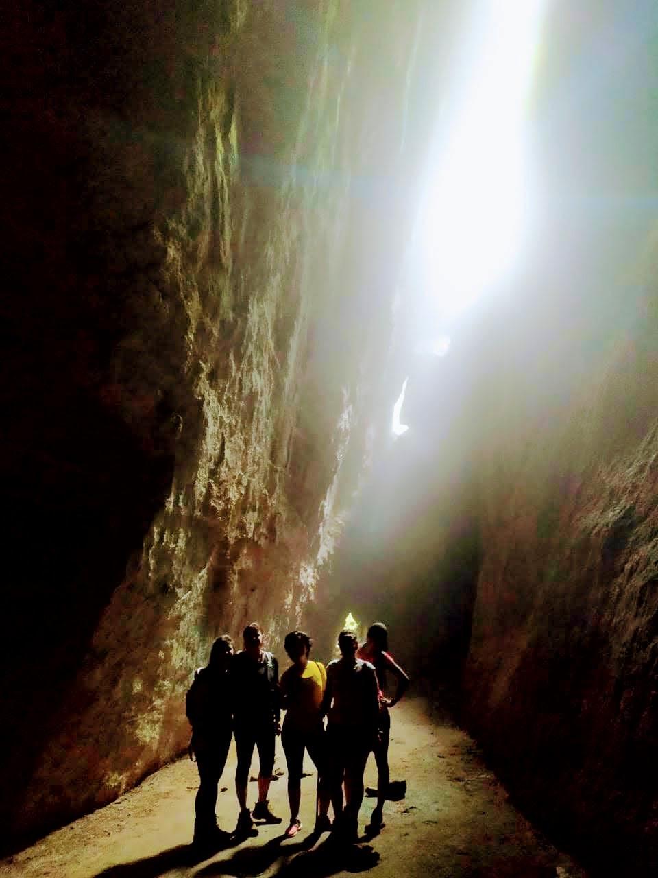 foto com cinco pessoas dentro de uma gruta