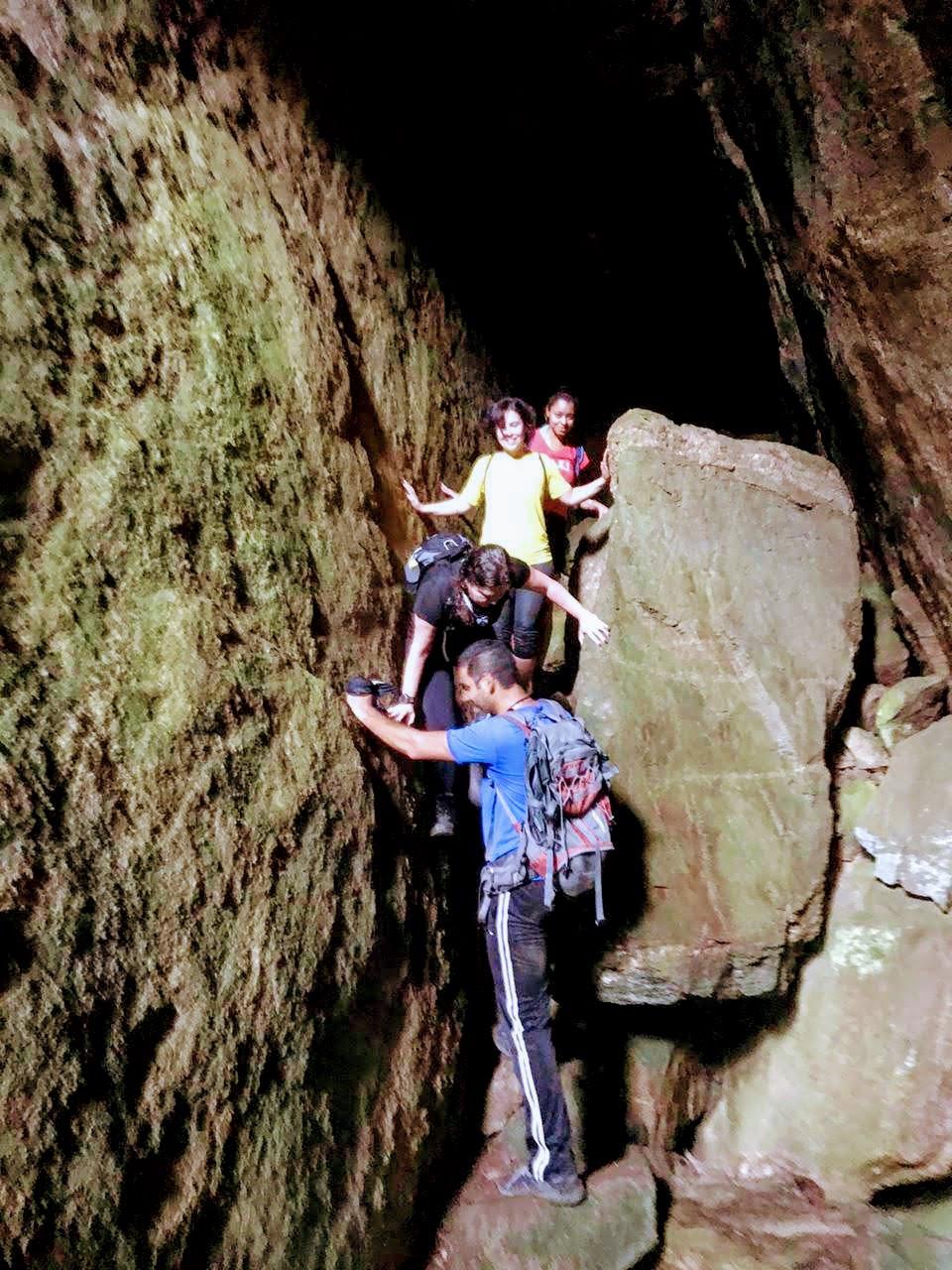 quatro pessoas dentro de uma gruta escalando