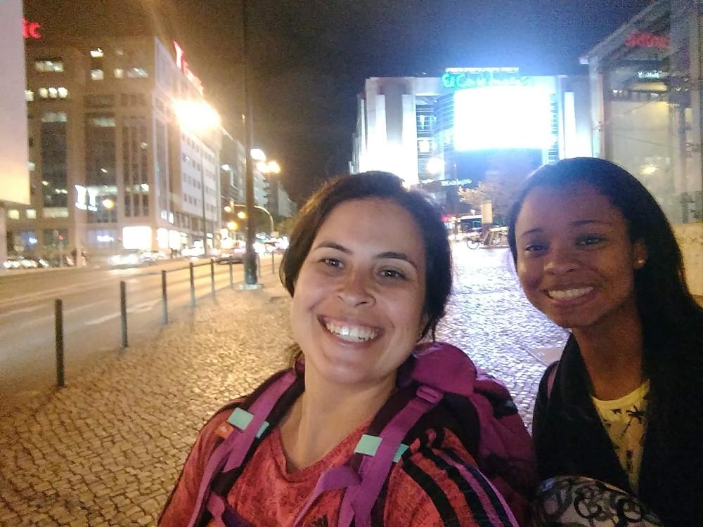 Duas garotas com mochilão sorrindo e tirando selfie à noite