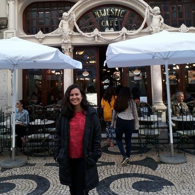 uma mulher sendo fotografada em frente ao café majestic