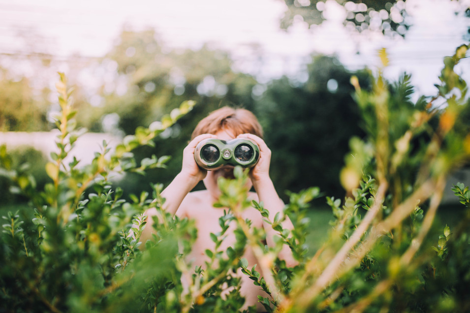 Lifestyle photo of a boy looking with binoculars.
