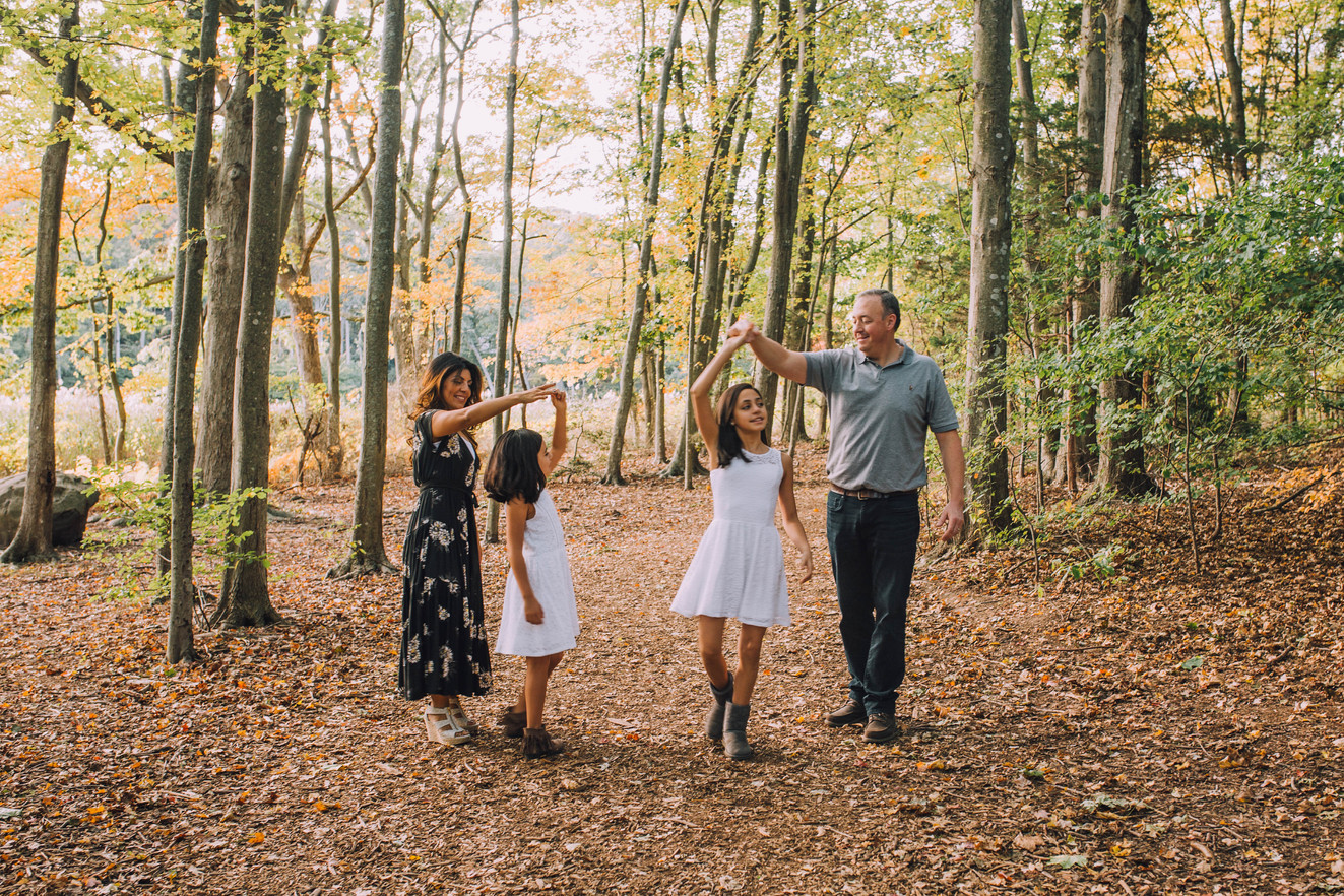 Lifestyle photo of a family dancing in the forest