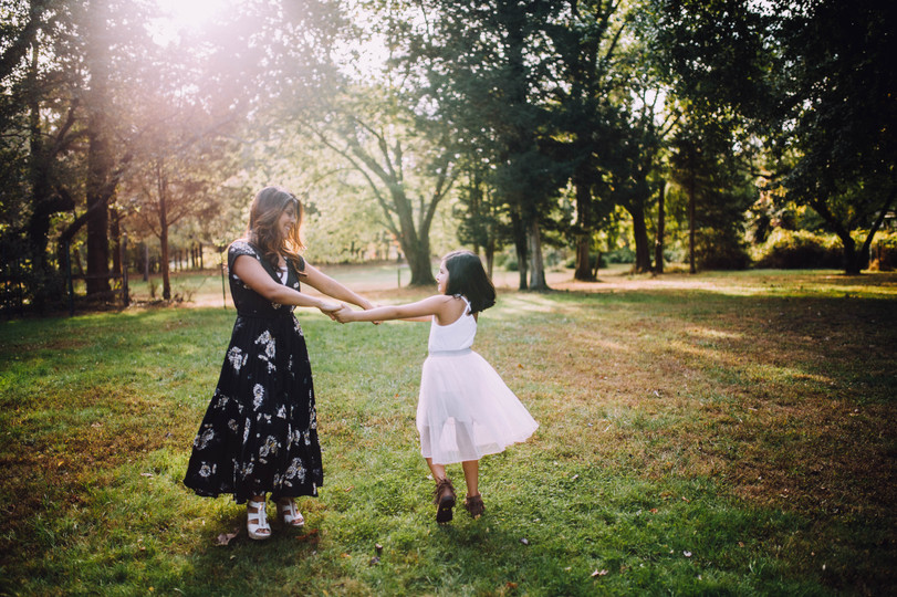 Lifestyle photo of a mother and a douther dancing outdoors