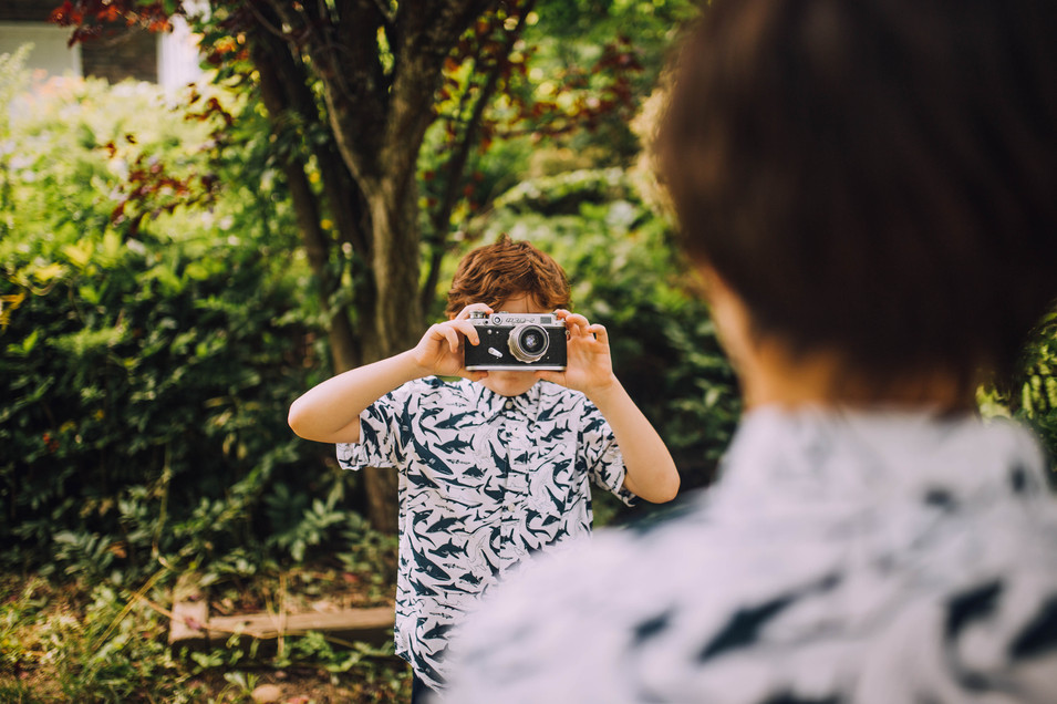 Lifestyle photo of a boy taking a picture with vintage camera