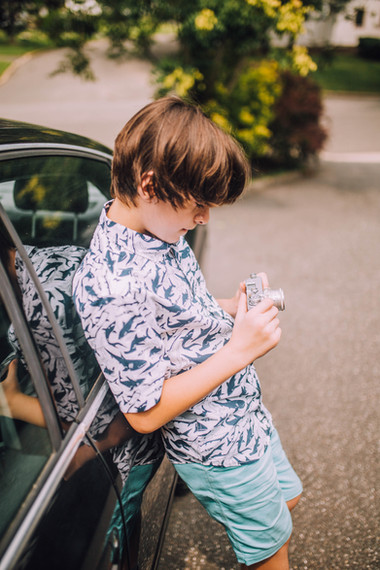 lifestyle photo of a boy looking at his vintange camera