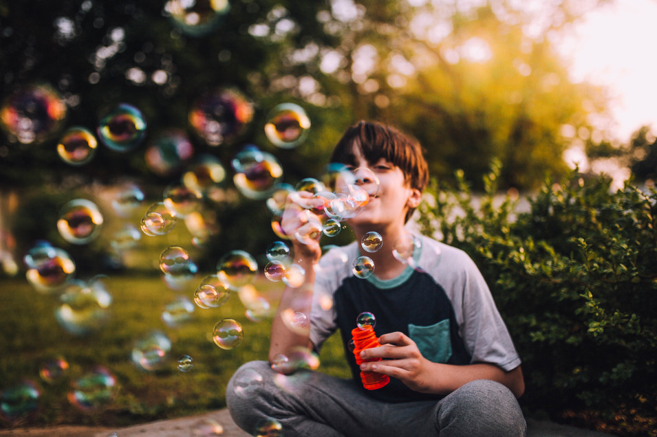 Lifestyle photo of a boy blowing bubbles
