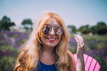 Blond woman smiling wearing aviator mirrored sunglasses