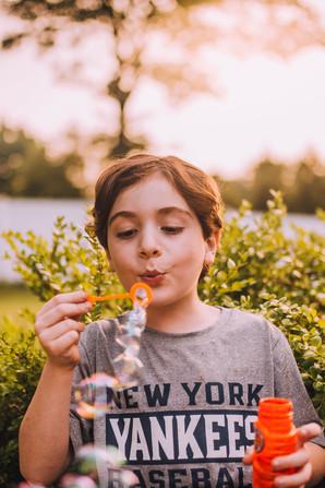 Lifestyle portrait of a young boy blowing bubbles