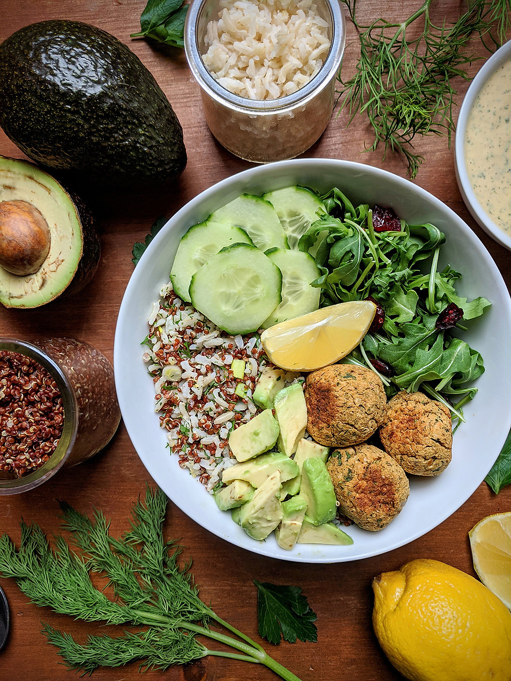Greens and Grains Bowl with Spicy Baked Falafel served with Creamy Sriracha Dill Dressing, Avocado, and English Cucumber