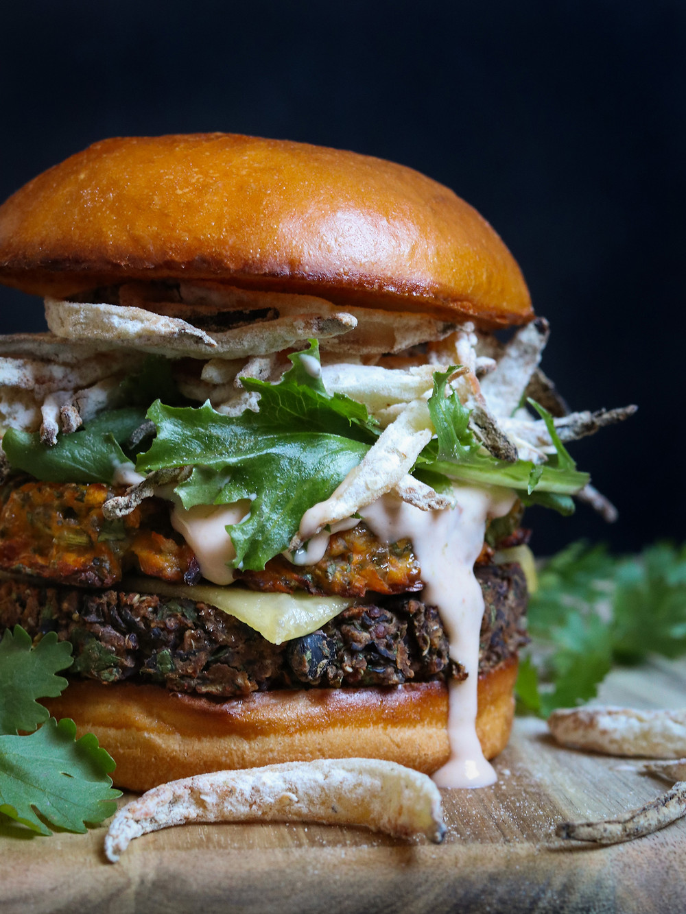 The Hybrid Burger served with Black Bean Burger, Sweet Potato Rösti, Crispy Onion Strips, Vegan Smoked Gouda, and Sriracha Aioli on a Brioche Bun
