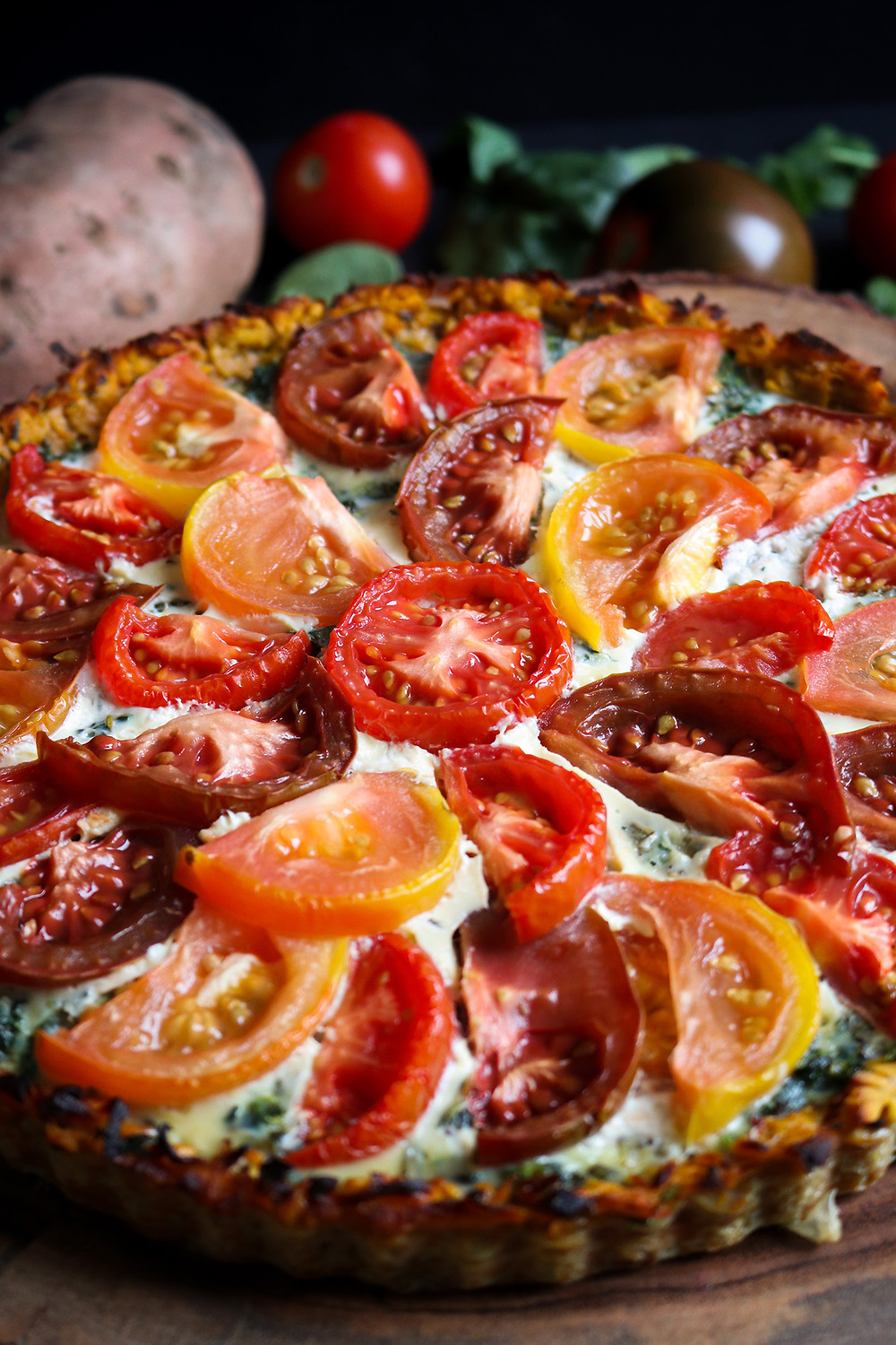 Rosemary and sage tomato tart with sweet potato crust, sautéed spinach and onions, and blue cheese