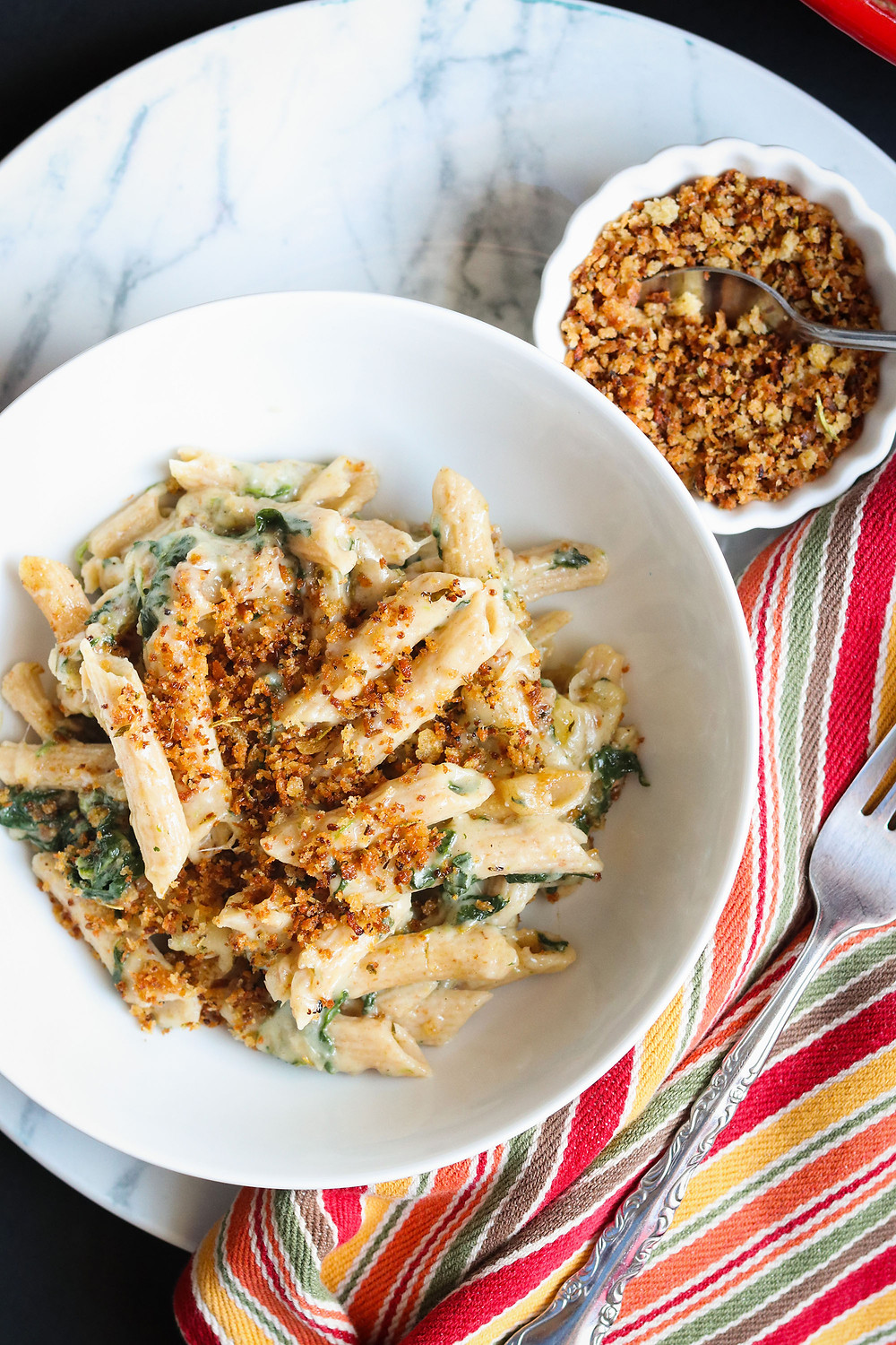 White Bean Mac n' Cheese with whole grain penne rigate, sautéed spinach, and rosemary garlic toasted bread crumbs