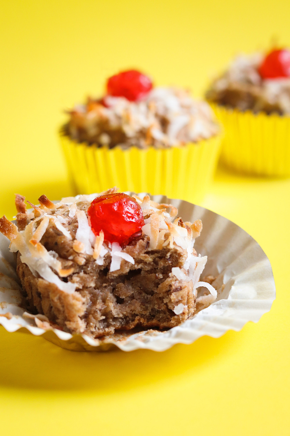 Vegan High Protein Tropical Banana Muffins garnished with Toasted Coconut and Red Cherries