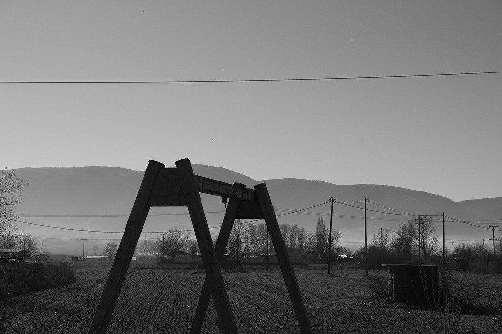 The swing. Rural land next to the urban and industrial landscape. The skeleton of an abandoned swing. Evoking a sense of suspension, swinging back to the past and forward to the present. And one more time, the wires… © DIMITRIOS GIOVIS
