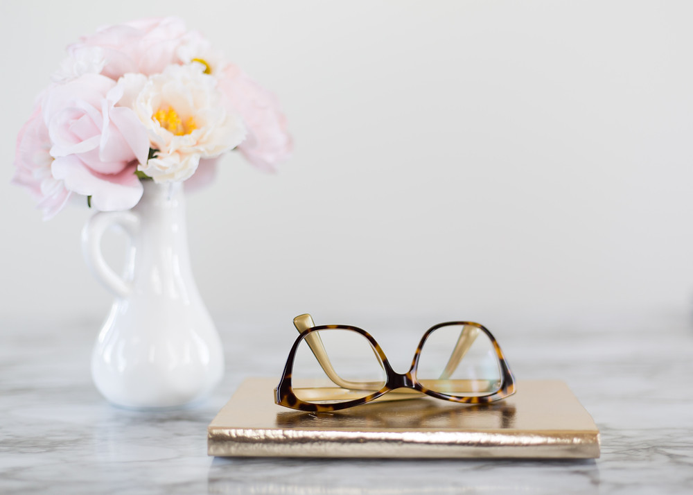 vase with pink flowers next to gold agenda and tortoise shell glasses