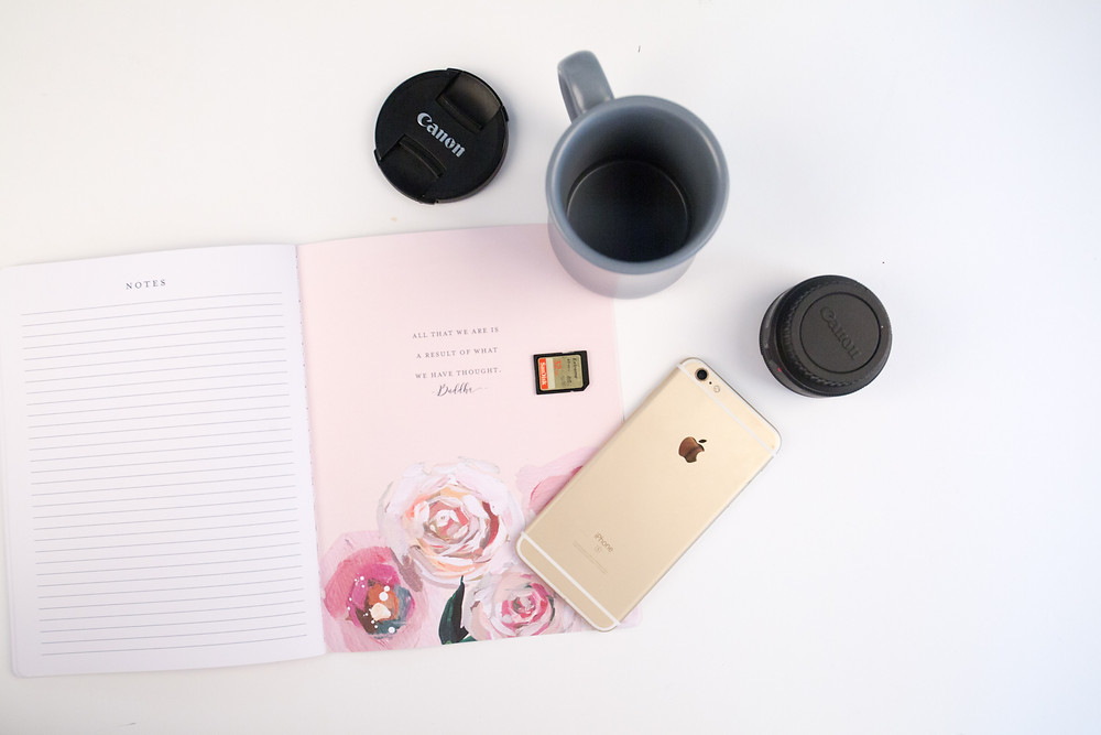 open planner, Canon lenses, coffee mug, iPhone