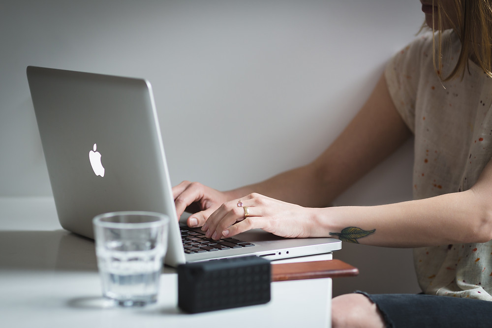 Woman typing on a MAC computer