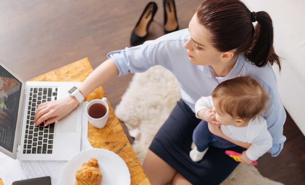 seated mom with infant on lap while typing on laptop