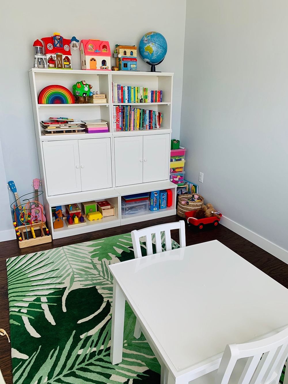 small table and chairs on rug next to bookshelf with kids' toys