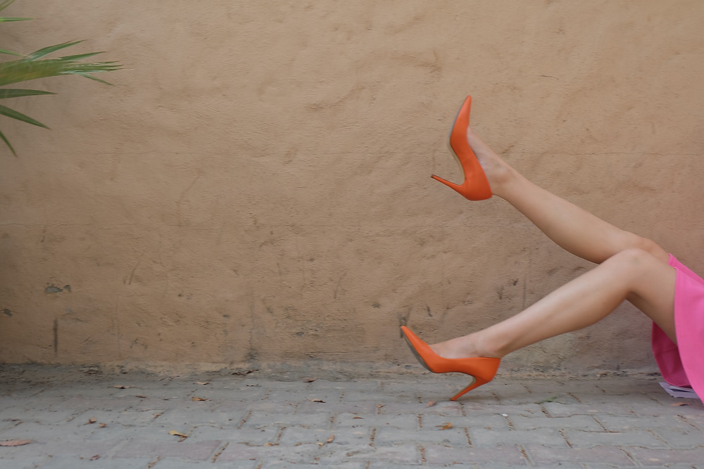 woman in pink dress kicking foot with orange high-heel shoe up in the air