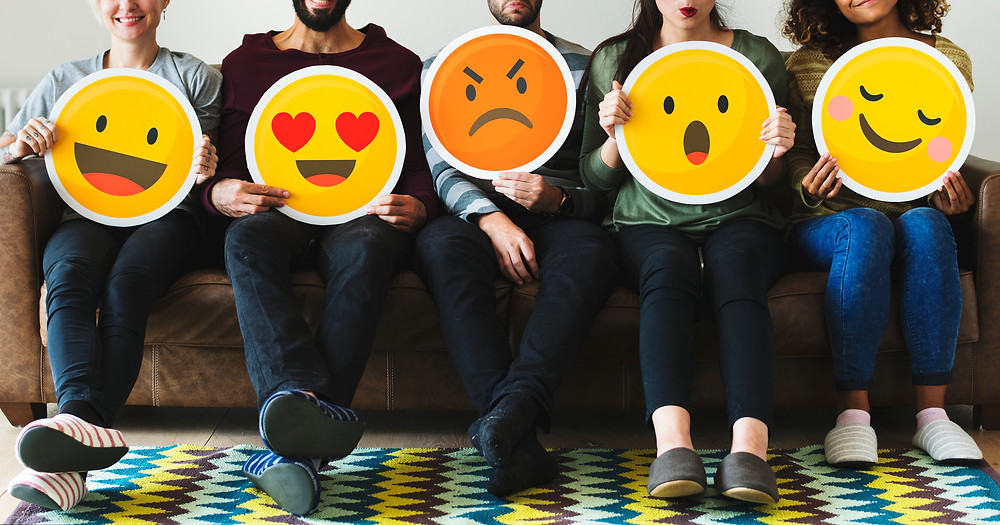 Five men and women seated on a couch holding emoji signs