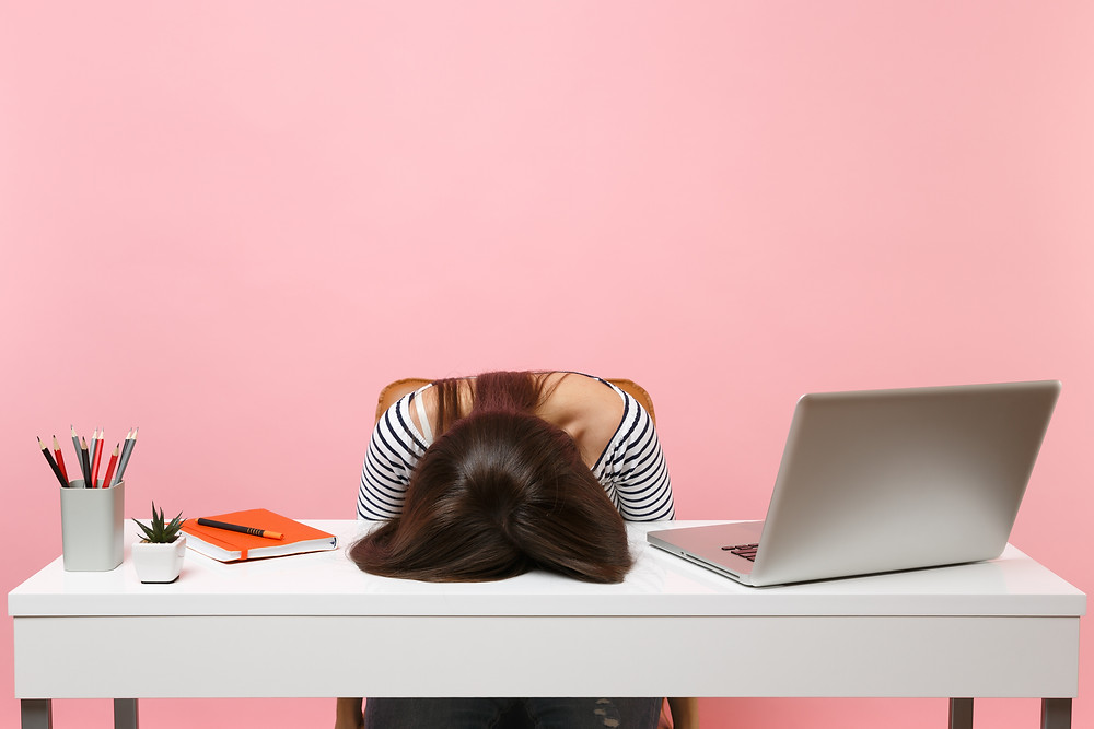 overtired and overstressed woman with face down on desk