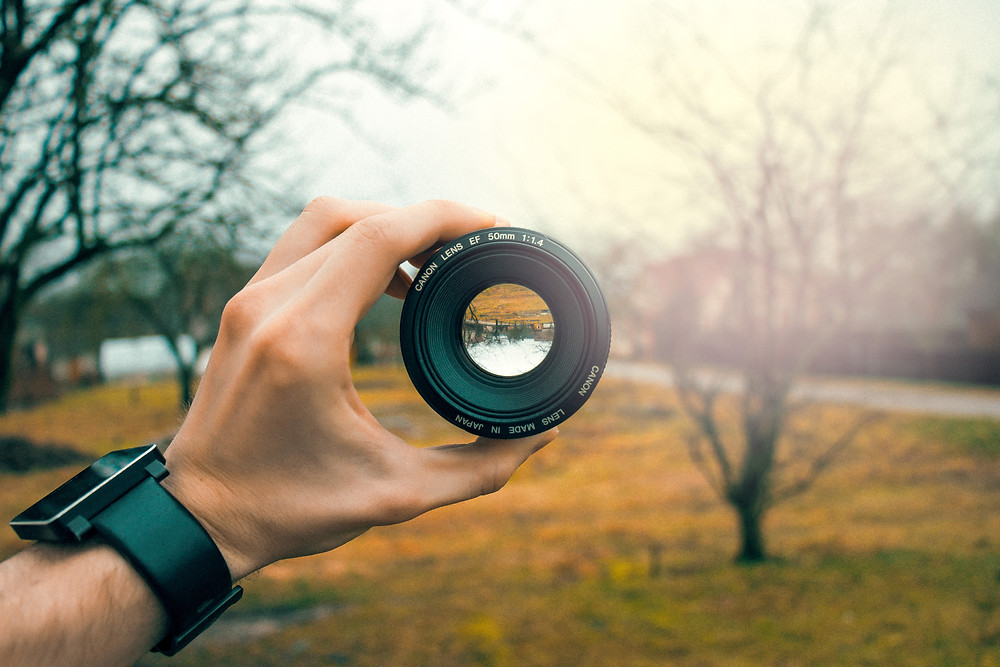 Man holding lens to focus on scenery
