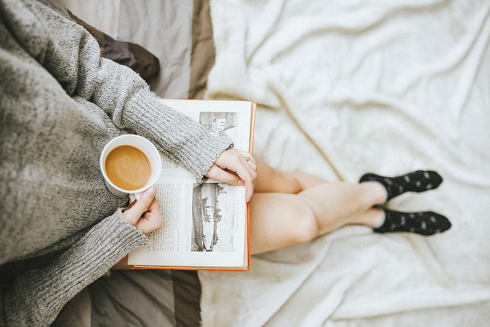 woman in bed reading book with coffee