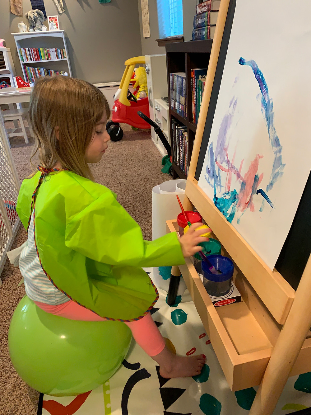 Mallory painting at her easel while I work