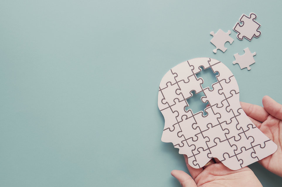 Hands holding brain with puzzle paper cutout, autism, memory loss, dementia, epilepsy and